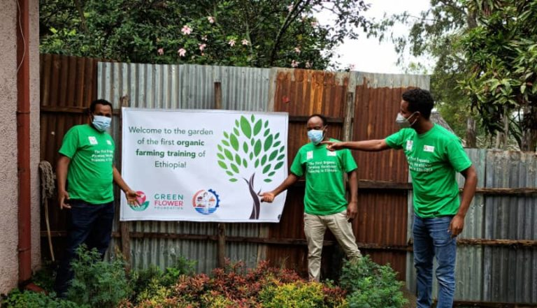 Men showing a banner of the tree planting campaign in the school garden