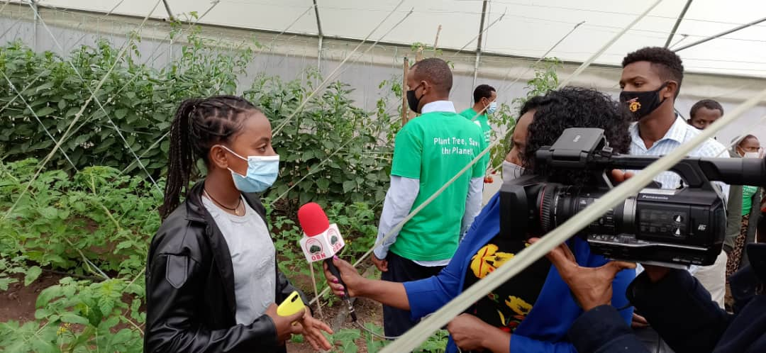 Student wearing mask talking in front of a media camera and journalist during the tree planting campaingn