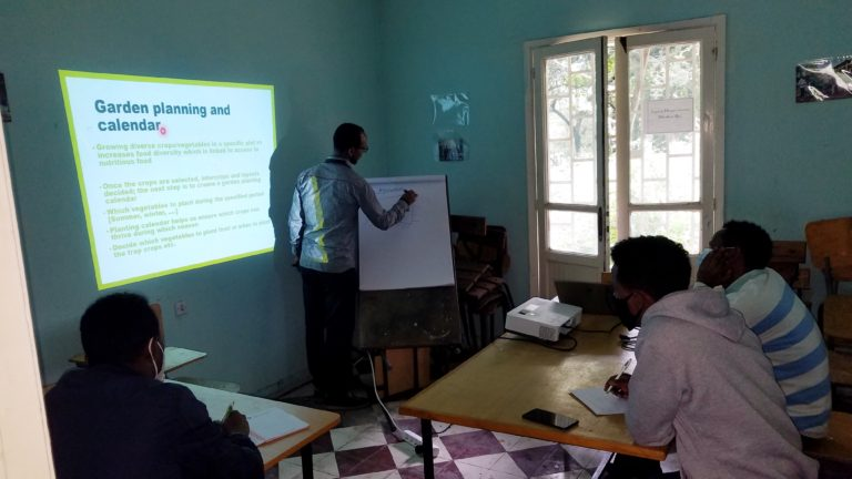 Teacher writing on a board about gardening for students